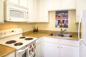 kitchen with white cabinets, white appliances, and brown countertops