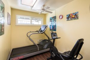 fitness center with two machines, ceiling fan, small window, posters on wall